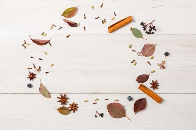 スパイシーな秋の背景。丸いフレームを作る乾燥した秋の花、葉、果実、シナモンスティック、クローブ、スローの組成物。白い木、平面レイアウトのトップビュー