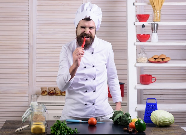 Spicy food concept male chef bearded cook eating red hot chili pepper organic food concept