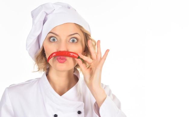 Концепция пикантной пищи - женщина-шеф-повар делает усы из красного острого перца чили. профессиональный повар в белом костюме держит красный острый перец чили как усы, глядя в камеру широко раскрытыми глазами. скопируйте пространство.