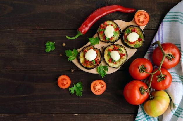 赤唐辛子、にんにく、ハーブ、モッツァレラチーズを添えたスパイシーな揚げ茄子のスライス。上面図。