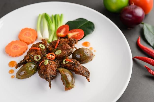 白い皿、タイ料理のスパイシーフライナマズ。