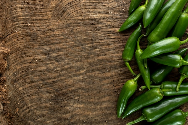Spicy green pepper on wooden background