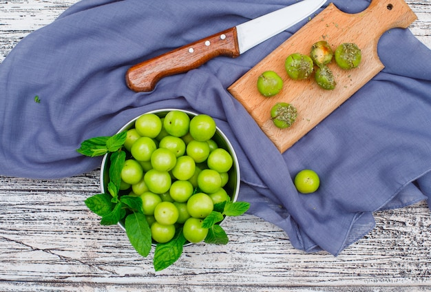 Spicy greengages with leaves in a metal saucepan and wood cutting board with knife high angle view on a grey wood and picnic cloth