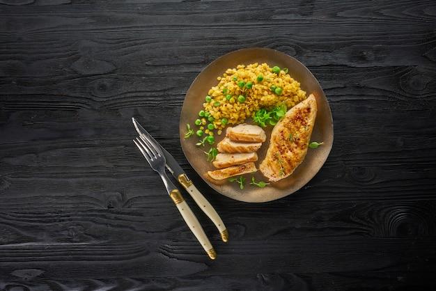 唐辛子とニンニクの暗い素朴な木製のテーブル、上面にスパイシーな焼き鶏の胸肉