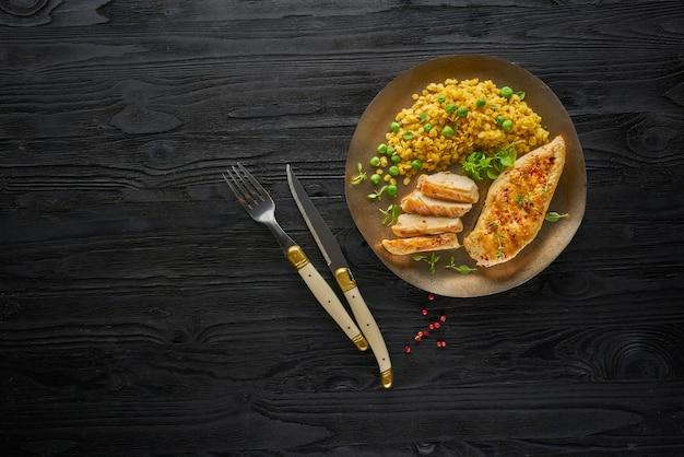 暗い素朴な木製のテーブル、上面に唐辛子とニンニクのスパイシーグリルした鶏ササミの胸肉
