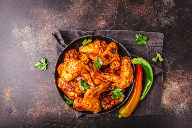 Spicy grilled chicken wings in tomato sauce in a black plate on a dark background.