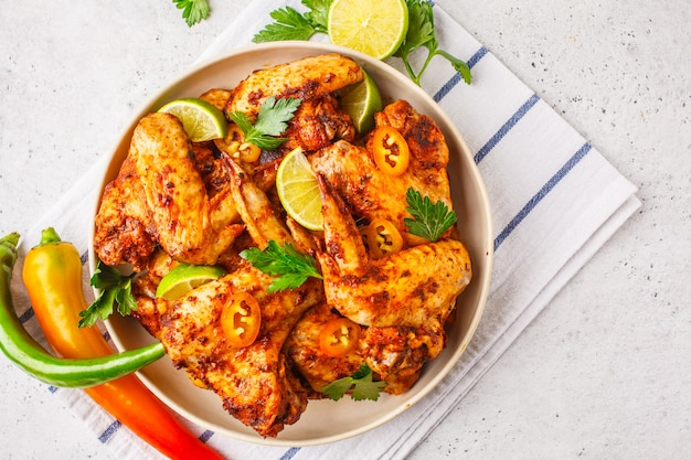 Spicy grilled chicken wings in tomato sauce in a white plate on a white background.