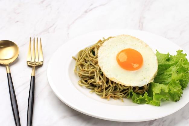 Пряная здоровая зеленая жареная лапша быстрого приготовления с сияющим солнечным бортовым яйцом и салатом на белой керамической круглой тарелке.