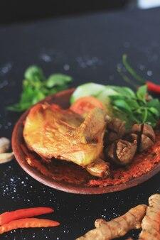 Острый горячий жареный цыпленок индонезийской кухни фон