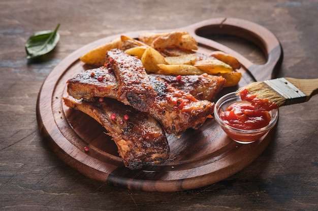 Spicy hot grilled spare ribs. grilled and smoked ribs with barbeque sauce on a carving board.