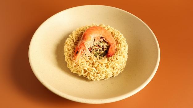 エビのスパイシーなインスタントラーメンスープ。エビのスープ、料理、食べ物。プレートに生の乾燥した円形の春雨。アジア料理。パスタ、その準備のために沸騰したお湯を注ぐのに十分です。