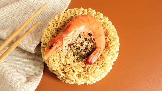 エビのスパイシーなインスタントラーメンスープ。エビのスープ、料理、食べ物。スパイシーな生の乾燥した円形の春雨。アジア料理。パスタ、その準備のために沸騰したお湯を注ぐのに十分です。