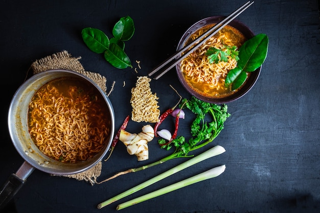 Spicy instant noodles soup and vegetables on a black background.