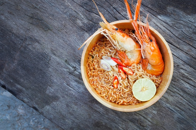 Spicy instant noodles soup with shrimp in wooden bowl on wood background