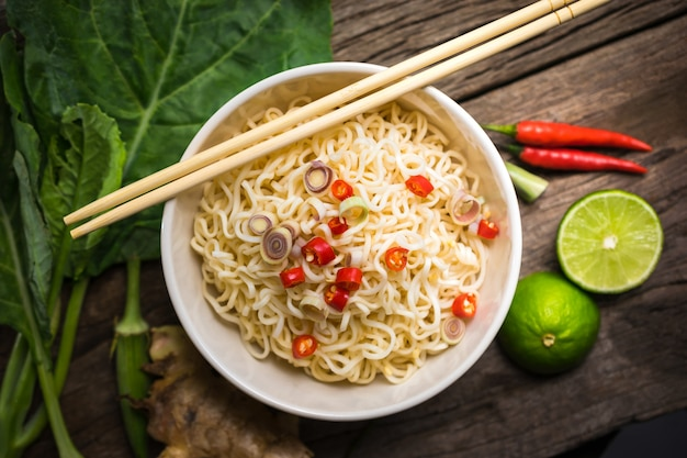Spicy instant noodles with vegetable in a bowl on wood board.