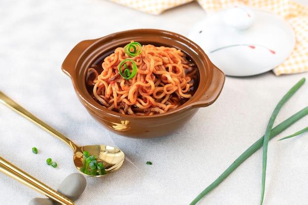 Острая корейская лапша рамен (рамен) на коричневой миске с кудрявым зеленым луком сверху, место для текста или рецепт. выбранный фокус