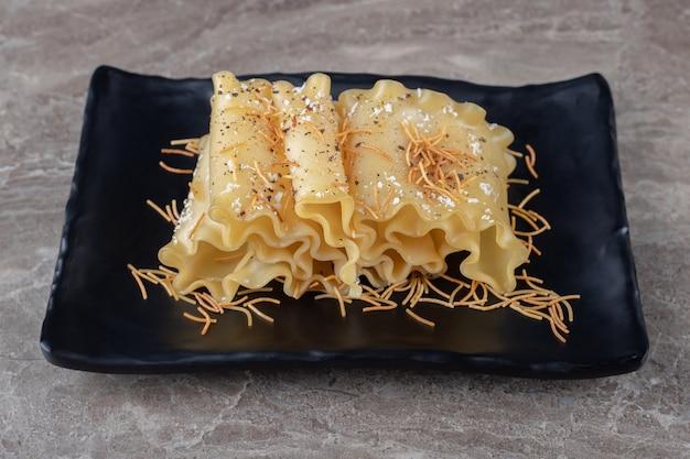 Острые листы лазаньи с тертой морковью на деревянной тарелке, на мраморной поверхности.