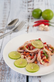 Spicy lemon squid with galangal, chilies, carrots, peppermint, spring onions and garlic on a plate on a white wooden floor.