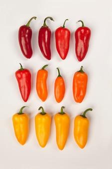 Острый маленький перц, создающий цветовый градиент от темно-красного до желтого, переходящий через светло-красный и оранжевый.