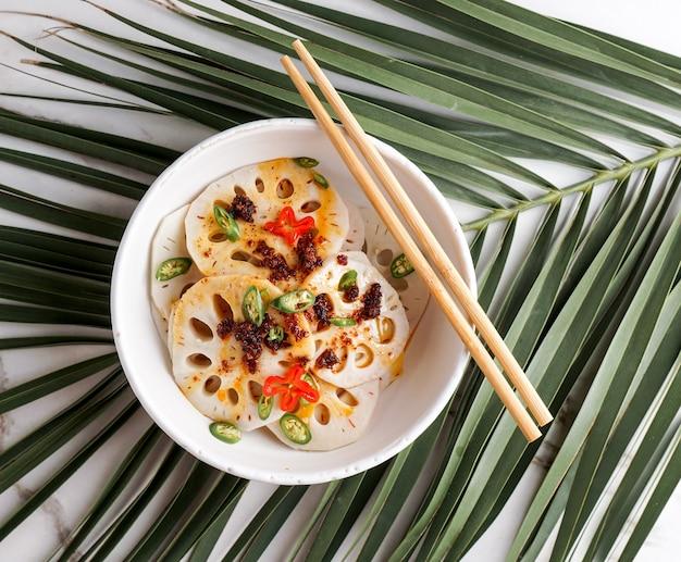 白い石の背景にスパイシーなレンコンのサラダ、アジア料理