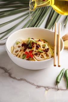 Острый салат из корня лотоса на фоне белого камня, азиатская кухня