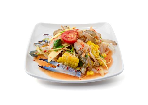 スパイシーなマンゴーサラダシーフード白で隔離、パパイヤサラダ、新鮮なエビと青カニ、タイ料理。