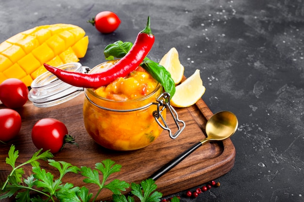 Spicy mexican salsa sauce with mango, chili, tomatoes and basil in a jar on the table