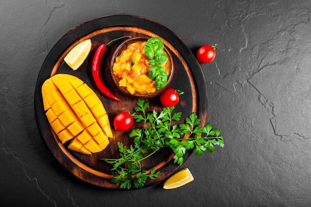 Spicy mexican salsa sauce with mango, chili, tomatoes and basil in a wooden bowl