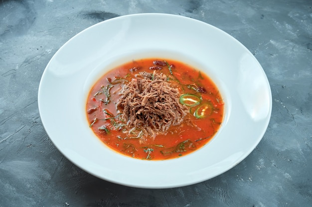 Spicy mexican soup - chili con carne with roast beef in a white plate on a gray background