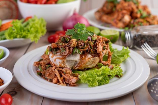 Острый фарш из курицы на белой тарелке с огурцом, салатом и гарнирами.