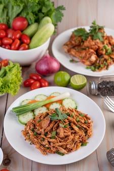 Pollo piccante tritato su un piatto bianco completo di cetrioli, lattuga e contorni.