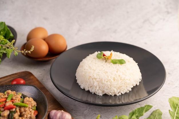 검은 접시에 매운 다진 돼지 고기와 쌀.