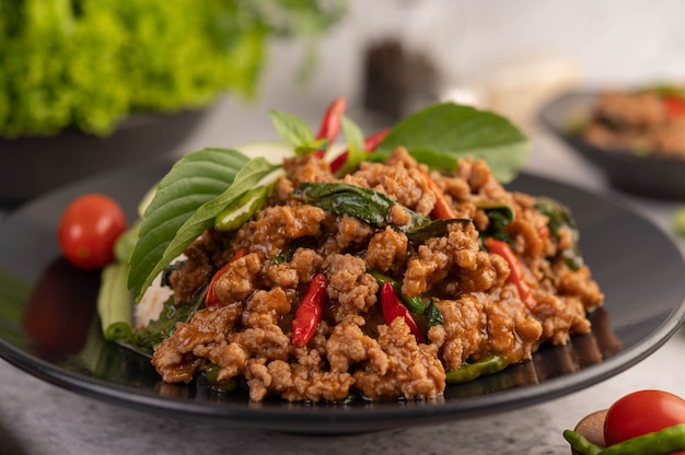 Spicy minced pork and rice on a black plate.