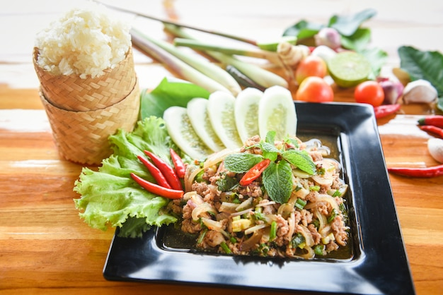 Spicy minced pork salad thai food with herbs and spices ingredients sticky rice tradition northeast food isaan.