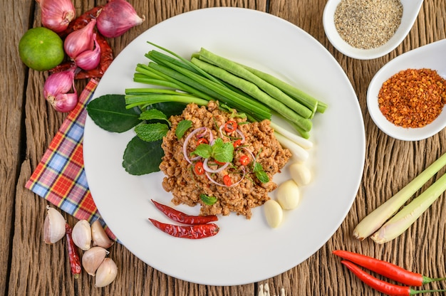 Spicy minced pork salad on a white plate with red onion, lemon grass, garlic, yardlong beans, kaffir lime leaves, and spring onion