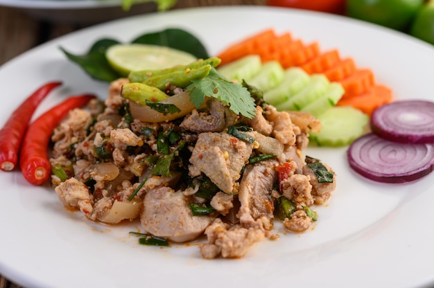 Spicy minced pork salad on a white plate on wooden table.