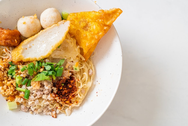 Spicy noodles with fish ball and minced pork (tom yum noodles)