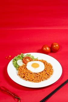빨간 배경에 토핑과 야채를 넣은 매운 국수