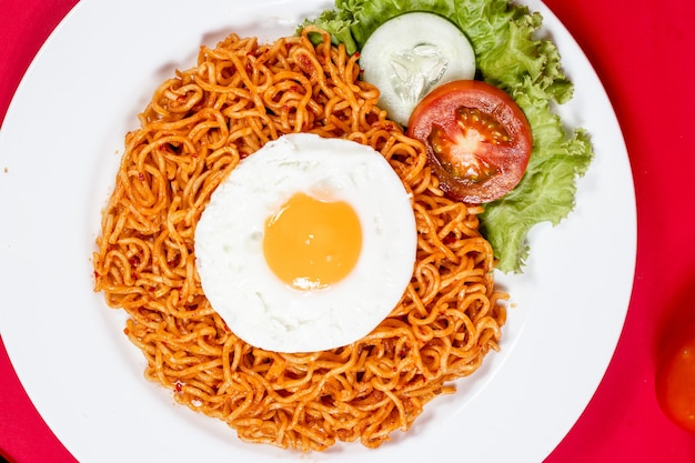Spicy noodles with topping and vegetables on red background