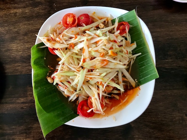 Spicy papaya salad in the banana leaf on the white plate top view