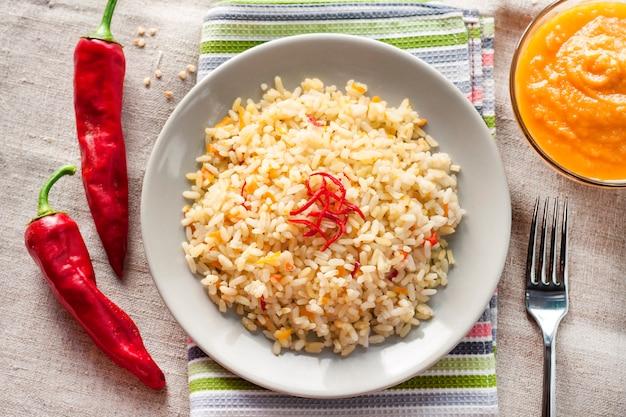 Пряный пропаренный рис с морковью, желтыми цукини и перцем чили на серой тарелке