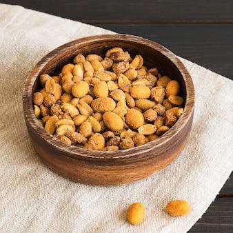 Острый арахис в деревянной миске