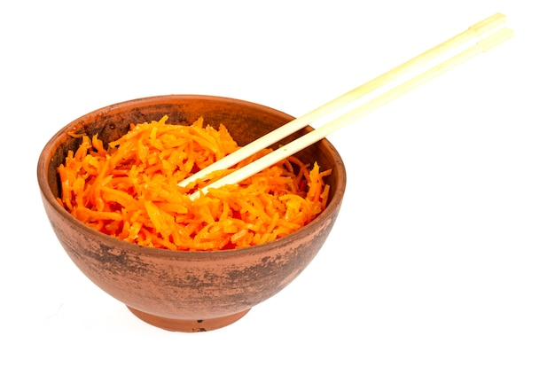 Spicy pickled carrots in bowl on white plate