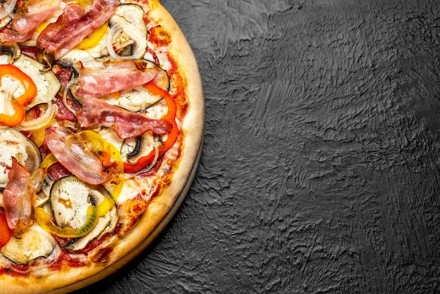 Spicy pizza on a black background, tomato-based with mozzarella