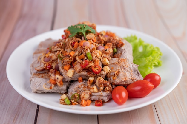 Spicy pork minced with tomatoes and lettuce on a white plate on a wooden table.