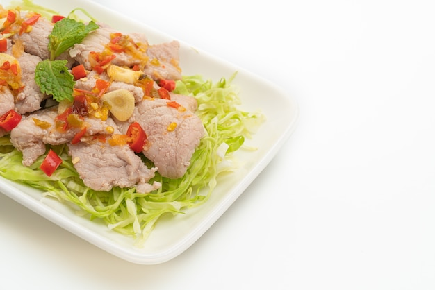 Spicy pork salad or boiled pork with lime garlic and chili sauce isolated on white
