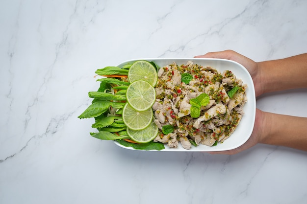 Spicy pork salad served with fresh crispy kale stalks thai food.
