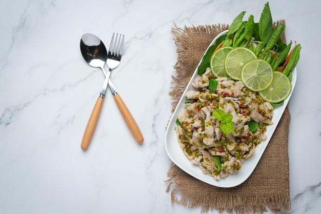 Острый салат из свинины подается со свежими хрустящими стеблями капусты. тайская кухня.