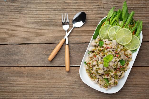 Insalata di maiale piccante servita con gambi di cavolo fresco croccante cibo tailandese.