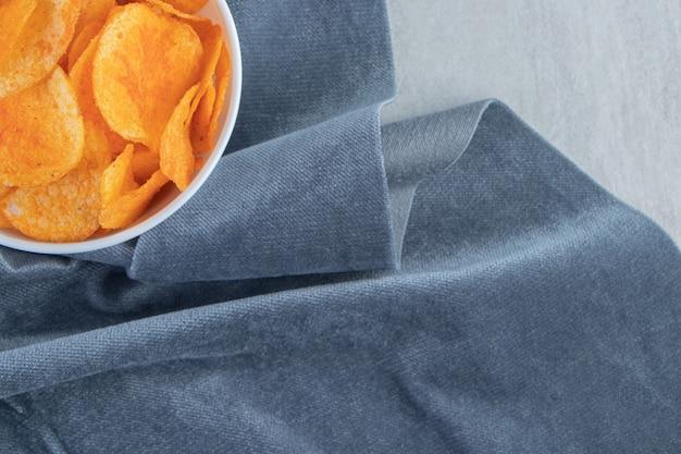 Patatine fritte piccanti e panno blu su pietra.